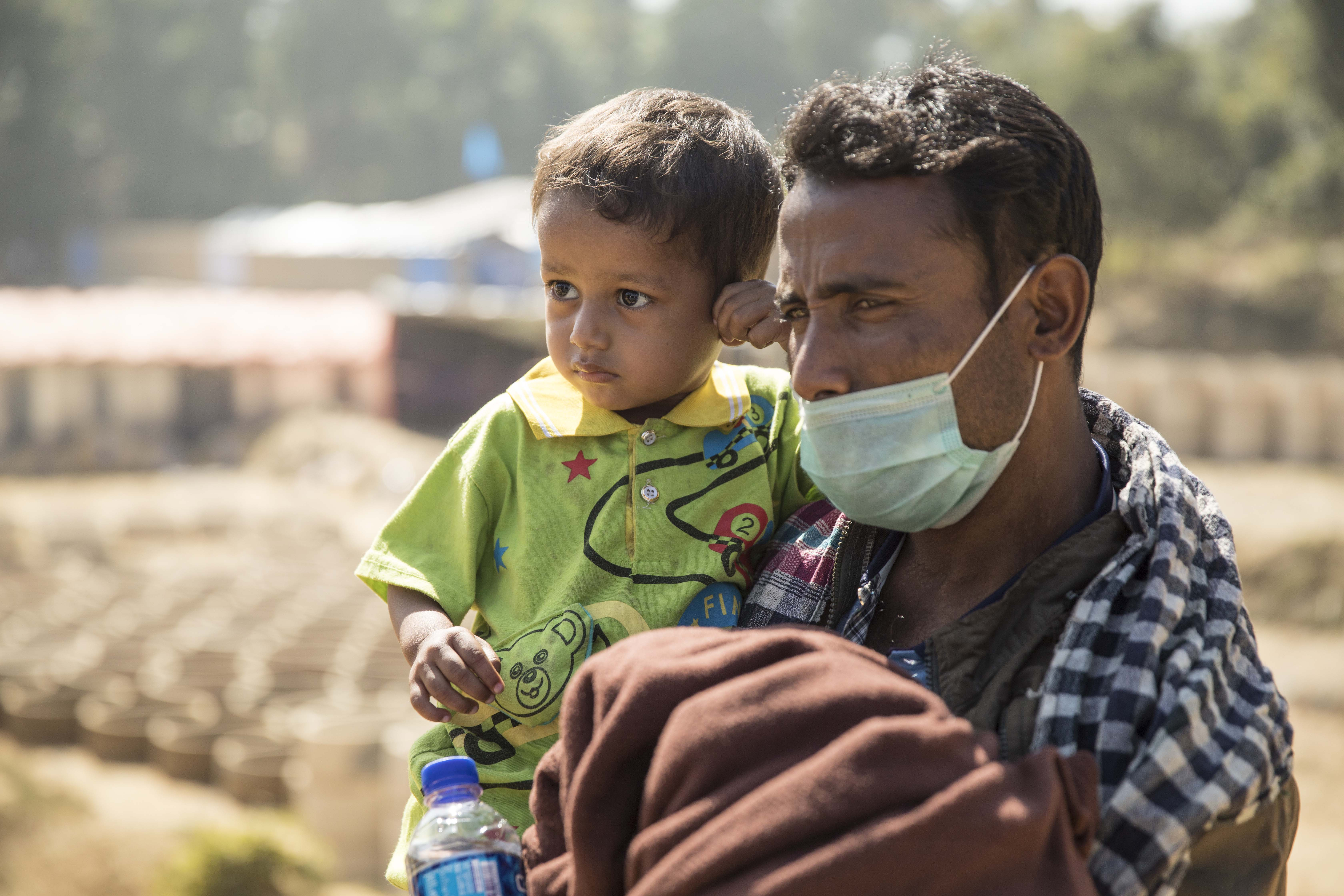 Mohammad clutches to his father as he carries him through Kutupalong camp