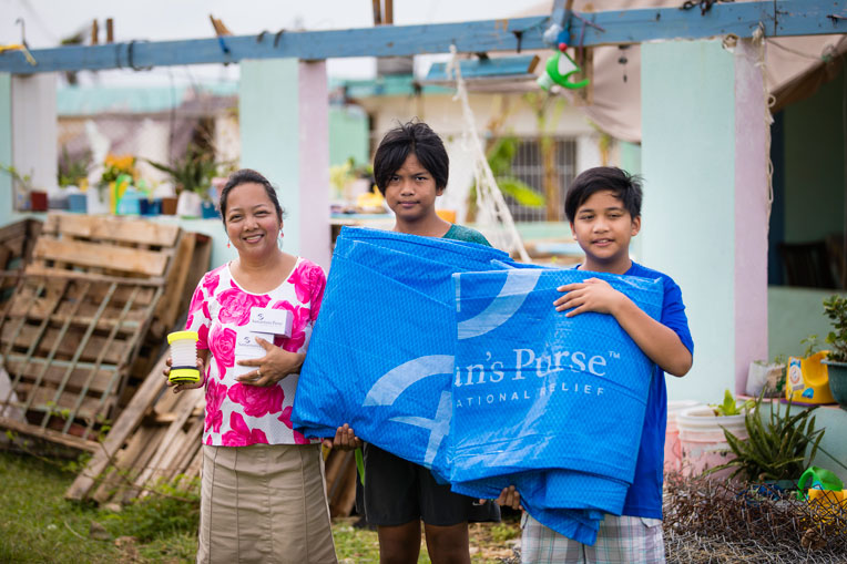Chielo, Marion, and Mitch received tarpaulin and solar lights from Samaritan's Purse.