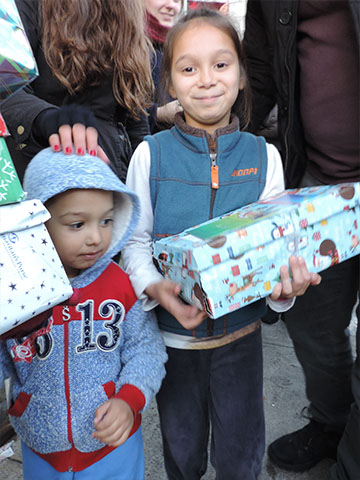 Children in a crowd with shoebox gifts