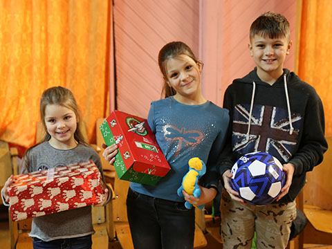 Children with shoebox gifts and football