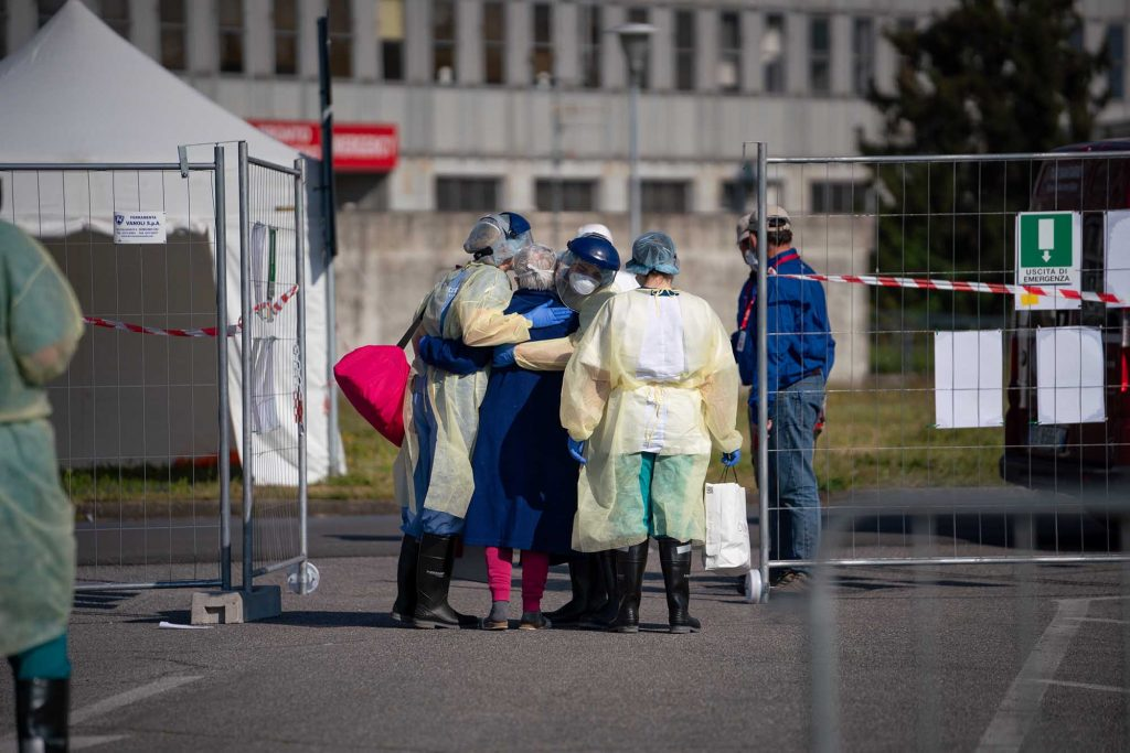 A patient embraces her nurses and translators as she is discharged from the SP field hospital in Cremona.