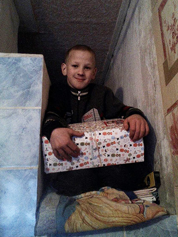 Young boy holding his shoebox