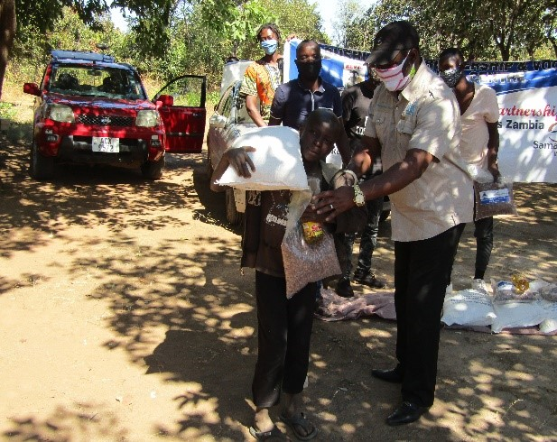 Siambango Mundia receiving food to feed his younger brothers and sisters