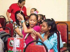 Girls opening shoeboxes in Saipan